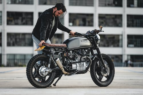 Selective Focus Photo of Man in Black Jacket Parking Black Honda Cafe Racer Motorcycle