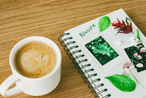 White Ceramic Cup Beside Spiral Notebook