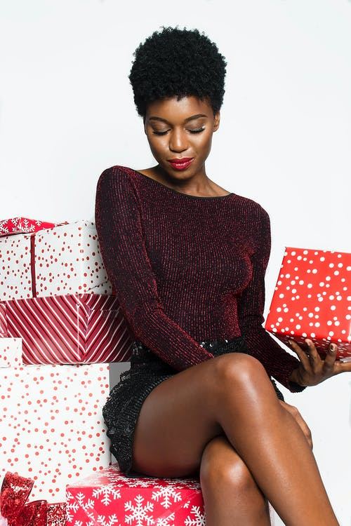 Photo of Woman Sitting on Gift Wrapped Boxes Posing While Holding a Present