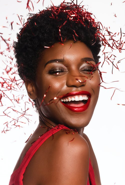 Close-up Photo of Smiling Woman with Her Eyes Closed Posing As Confetti Drops Down Her Face