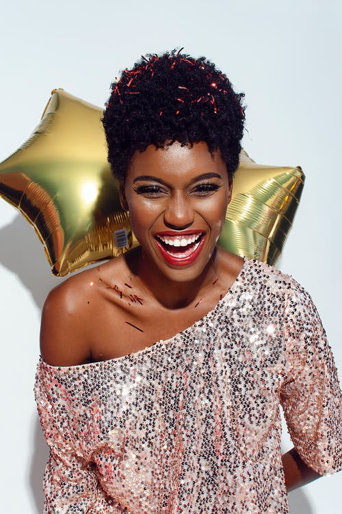 Photo of Laughing Woman with Confetti on Her Hair and Shoulders Posing In Front of White Background While Holding Golden Star Balloons Behind Her Back