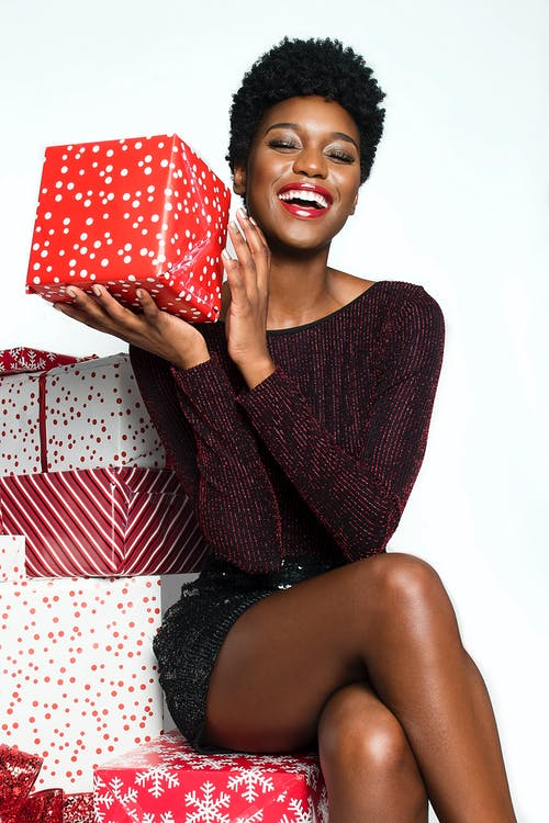 Photo of Smiling Woman with Her Eyes Closed Sitting on Gift Wrapped Boxes Posing While Holding a Present