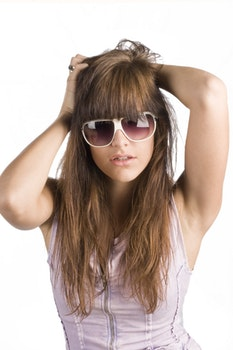 Portrait of Woman Wearing Sunglasses Standing Against White Background
