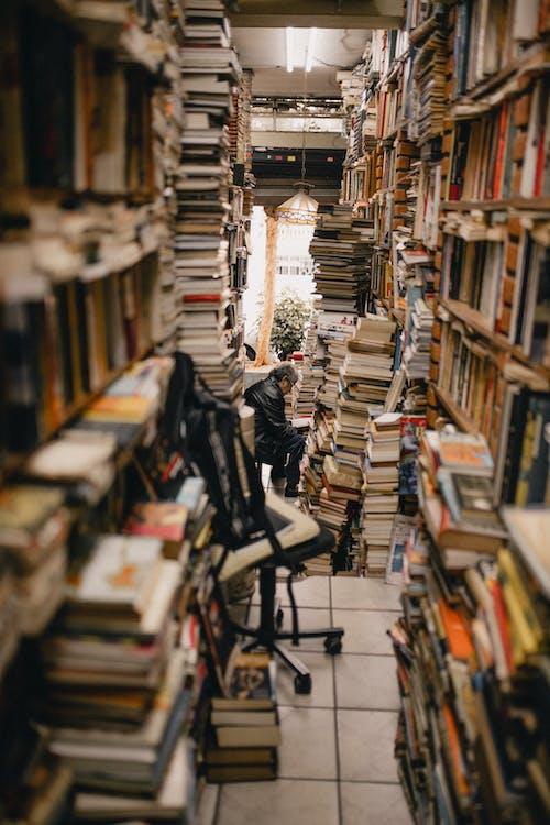 Man Sitting in Floor of Room Full of Books