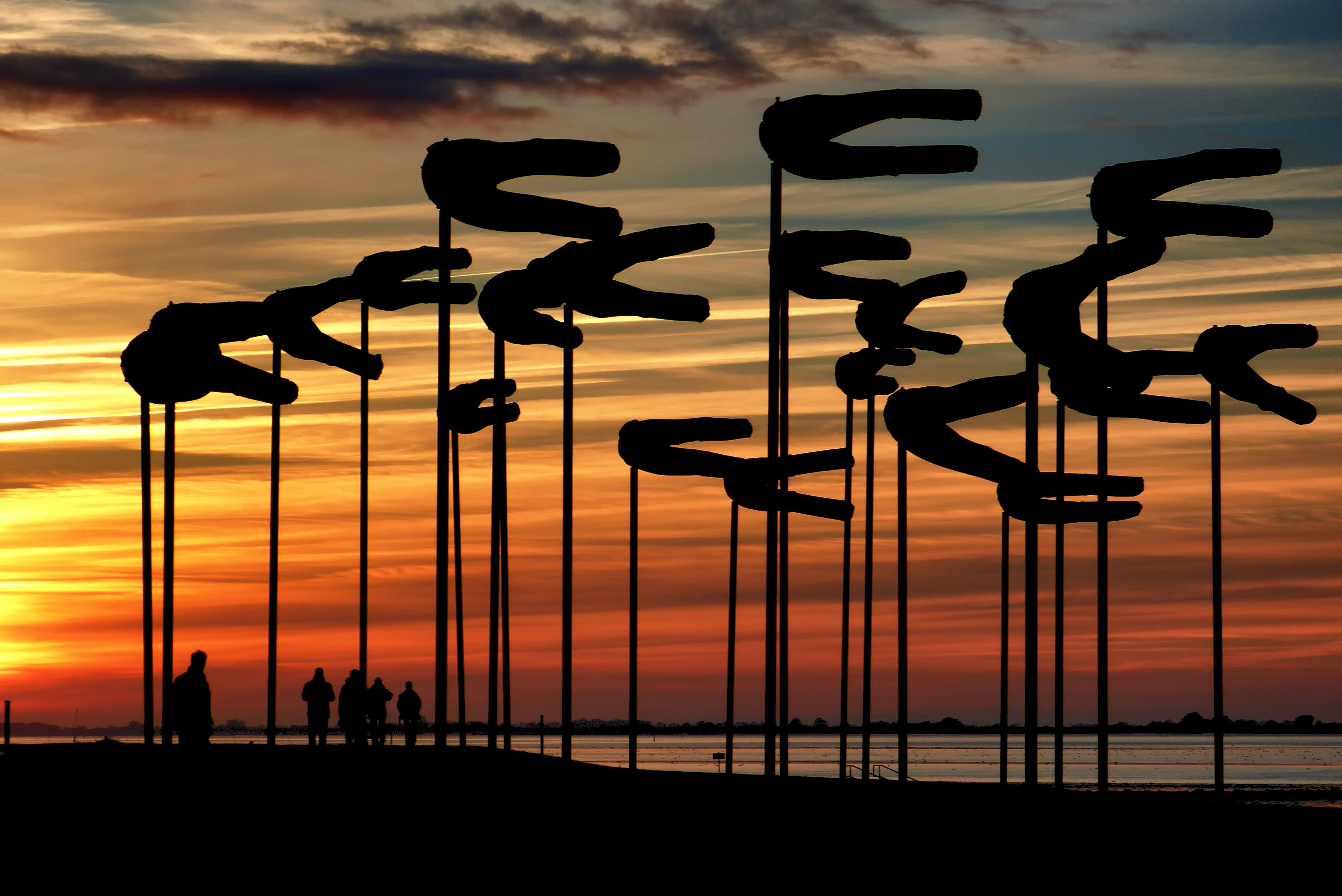 Silhouette Parasols Against Dramatic Sky during Sunset