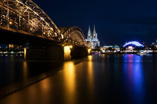 Lighted City Skyline Across River With Metal Bridge