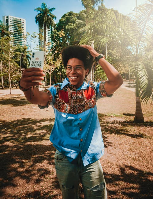 Photo of Smiling Man Taking a Selfie With Palm Trees in the Background