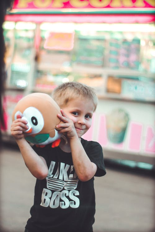 Selective Focus Photo of Smiling Boy Holding Brown Plush Toy