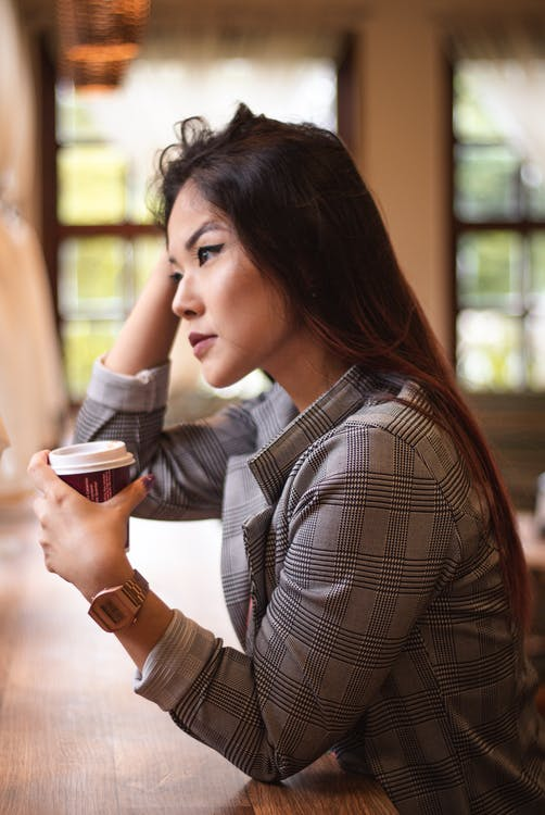 Selective Focus Side View Photo of Woman Sitting by Table Holding Plastic Cup Looking into the Distance