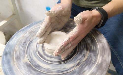 Person Making Pottery in Room