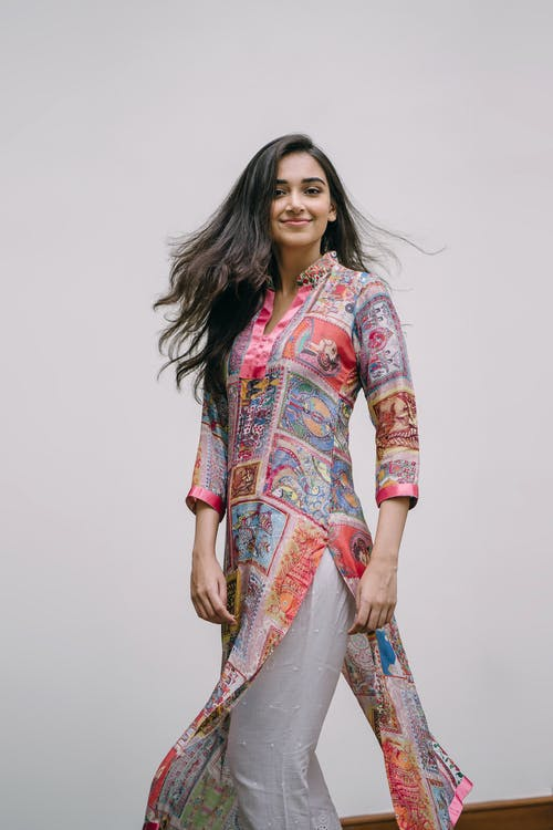 Photo of Smiling Woman in Floral Salwar Kameez Posing In Front of Gray Background