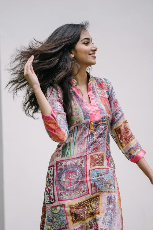 Side View Photo of Smiling Woman in Floral Salwar Kameez Flipping Her Hair While Posing In Front of Gray Background