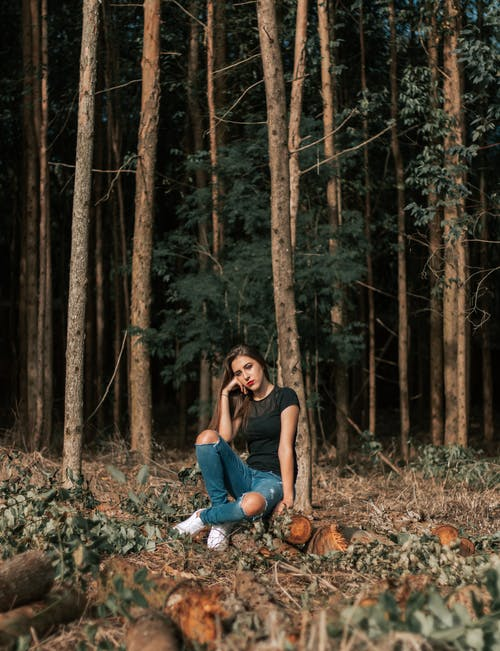 Photo of Woman in the Woods Sitting on Log