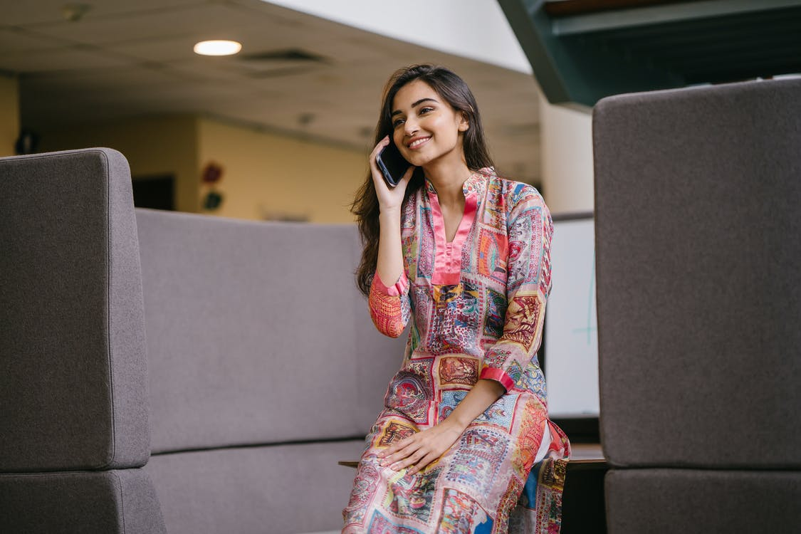 Photo of Smiling Woman in Floral Salwar Kameez Talking on Phone While Sitting on Edge of Wooden Table