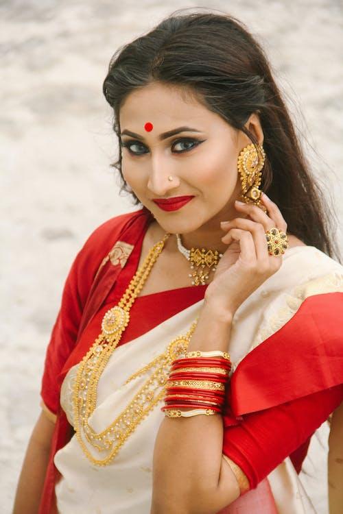 Fotobanka sbezplatnými fotkami na tému 20-25 ročná žena, usmievavá žena, žena na sebe červené šaty, žena na sebe zlaté šperky