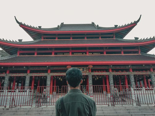 Man Standing in Front of Grey and Red Pagoda