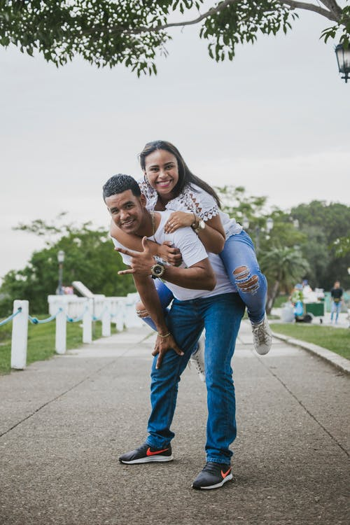 Photo of Man Giving Woman a Piggyback Ride