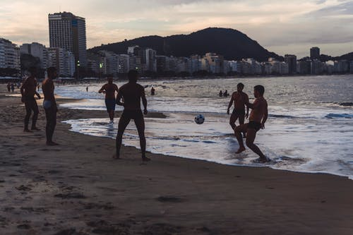 Men Playing Ball By The Seashore