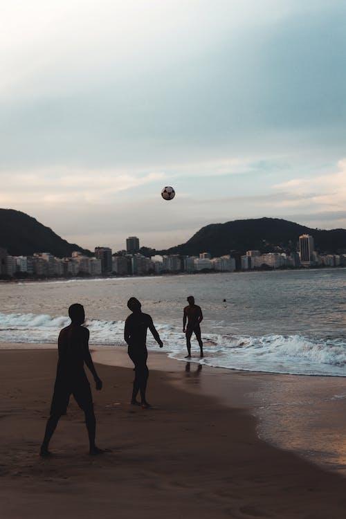 Three Men Playing Ball By The Seashore