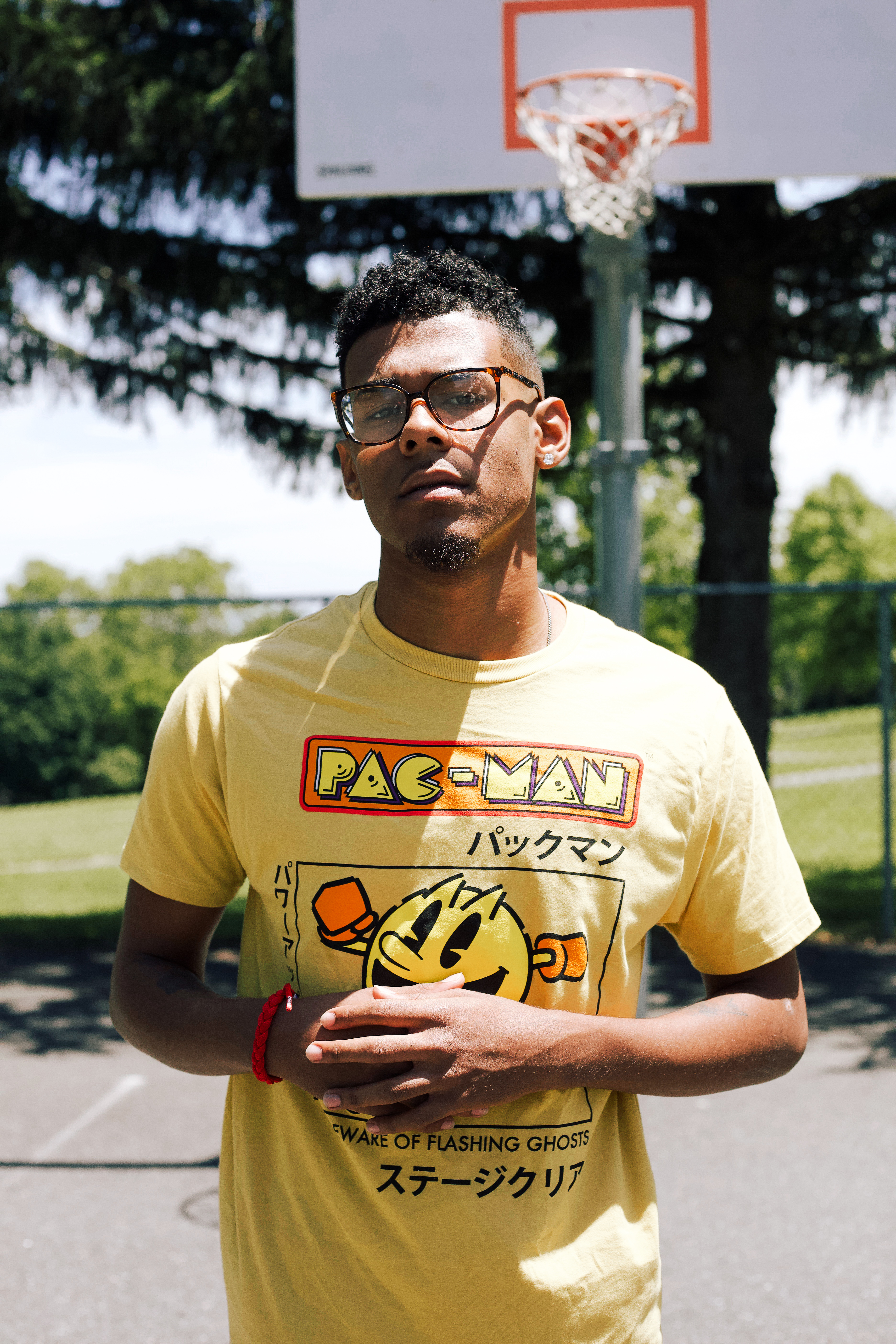 Photo of Standing Man in Yellow Pac-man T-shirt Standing in Basketball Court
