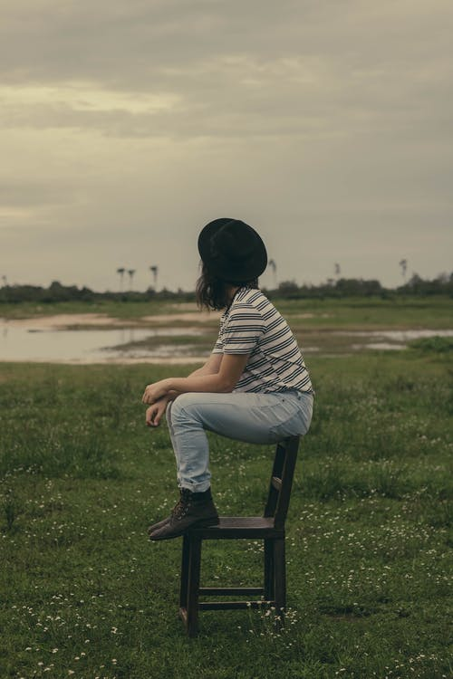 Photo of Woman Sitting on Brown Wooden Chair In the Middle of a Grass Field Looking Away