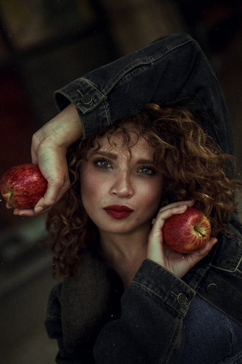 Photo of Woman Wearing Blue Denim Jacket Posing With Two Red Apple