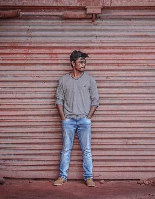 Photo of Man in Gray Long-sleeved T-shirt and Blue Jeans Posing In Front of Roll Up Door Looking Away