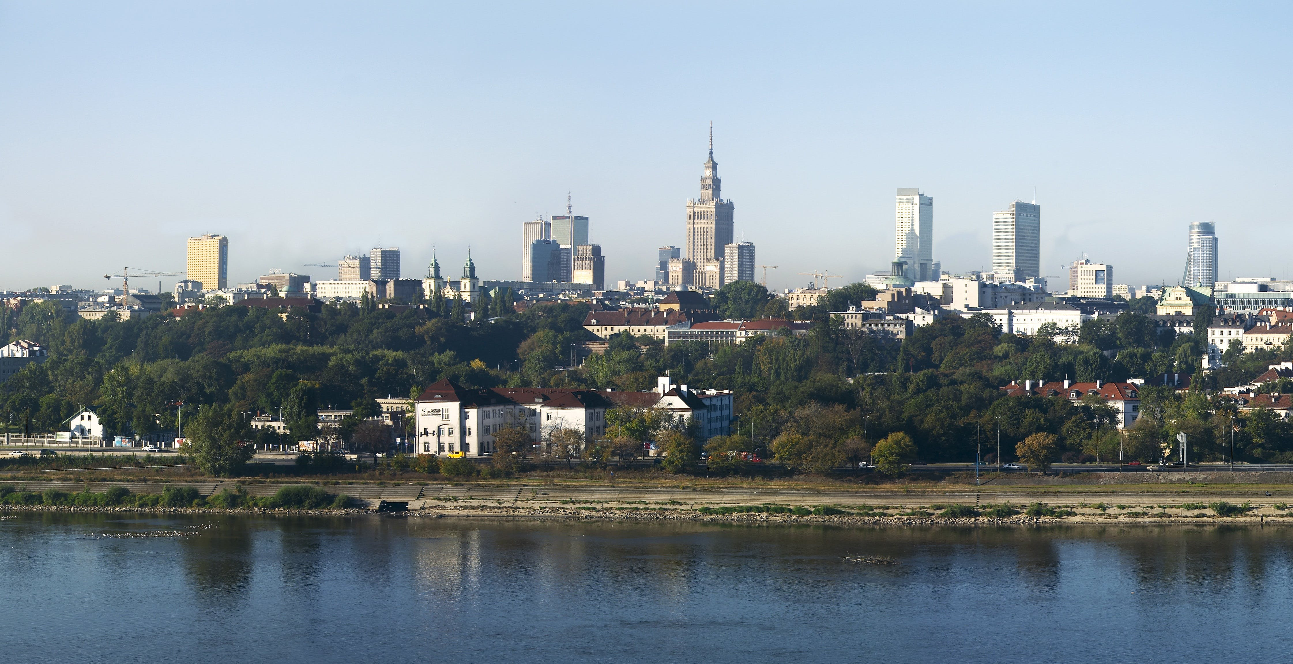 View of City by Lake Against Clear Sky