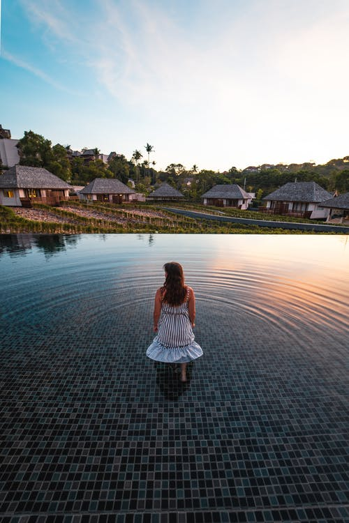 Back View Photo of Woman in White Dress Standing in the Middle of an Infinity Pool Looking at Resort Cottages