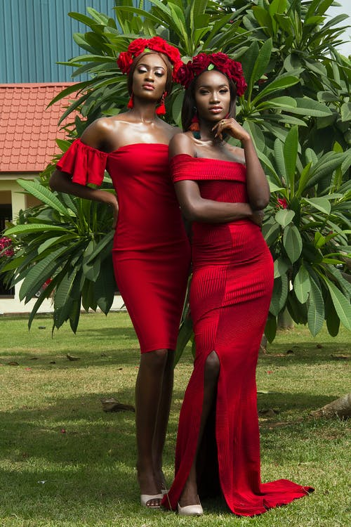 Photo of Two Beautiful Women in Red Dresses and Red Flower Crowns Posing In Front of Green-leafed Tree