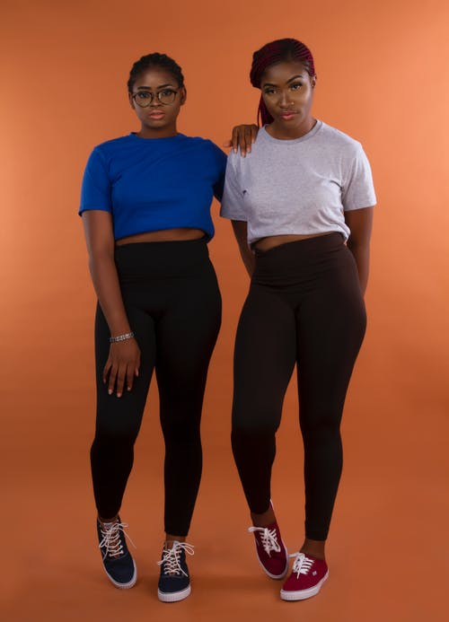 Photo of Two Women in Leggings and T-shirts Posing In Front of Orange Background