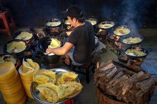 Photography of Man Cooking Surrounded by Woks