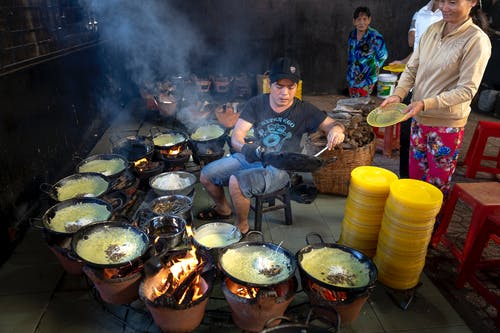 Man Cooking On Different Pots