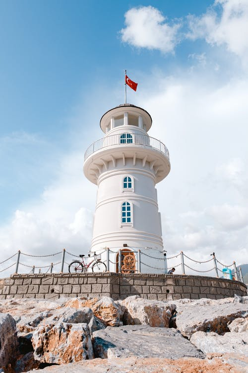 Red Flag On Top Of A White Lighthouse
