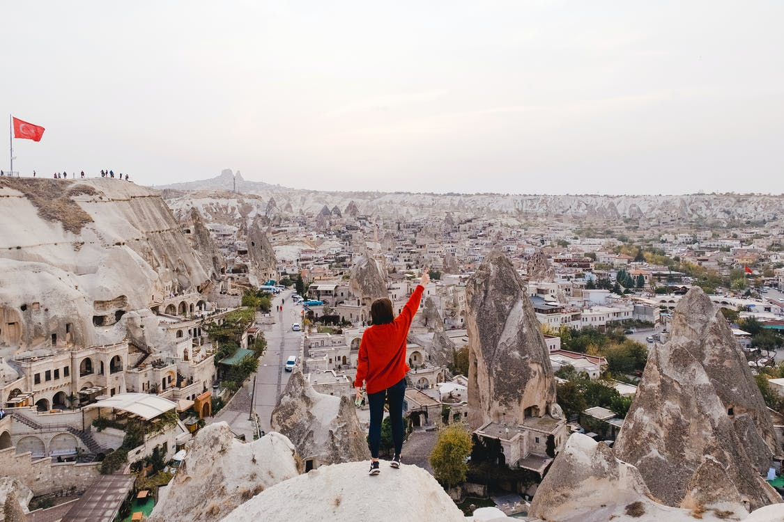 Person Wearing Red Long-sleeved Shirt Standing on Rock