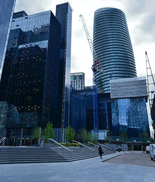 Безкоштовне стокове фото на тему «архітектура, багатоповерхова будівля, жінка, жінка, що йде перед висотних будівель»