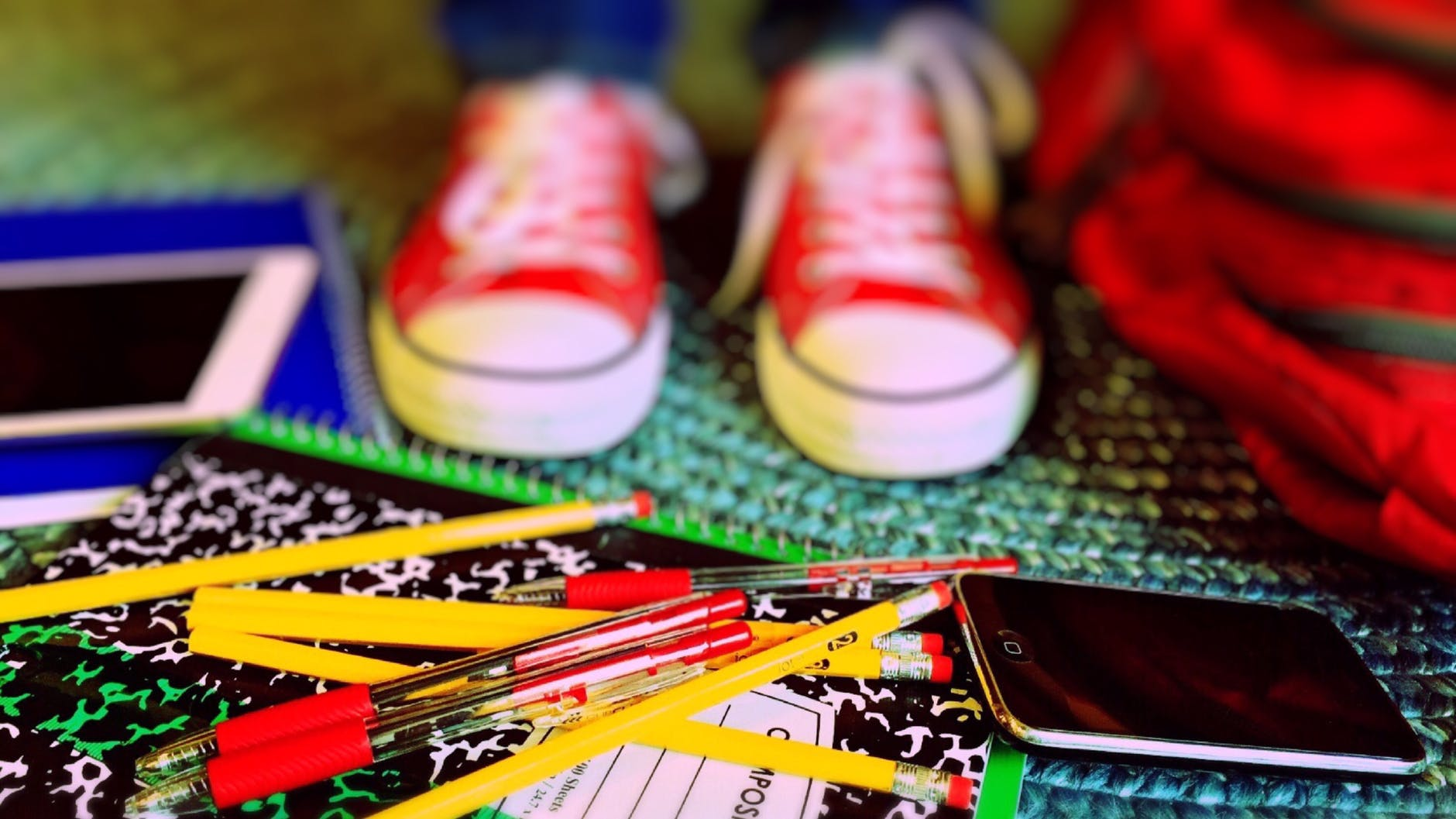 Kid's red sneakers, lots of pencils & pens scattered around the feet, mobile phone and tablet in the background.
