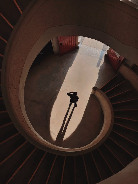 Person Standing Below A Spiral Staircase