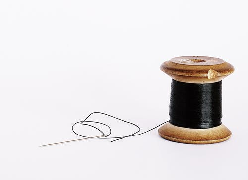 Black Thread On A Wooden Spool