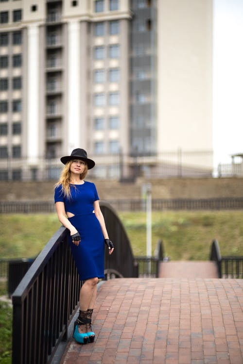 Selective focus photo of a woman in blue dress and a hat leaning on metal railings