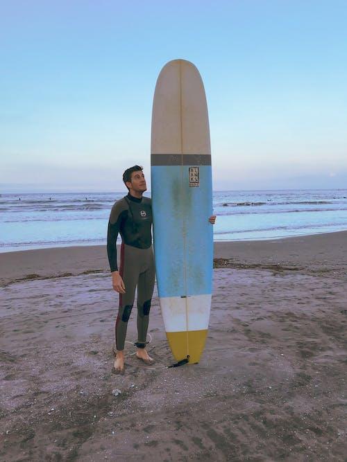 Man molding surfboard on the beach