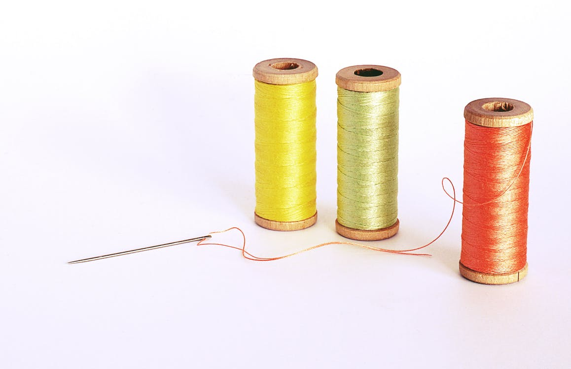 Needle And Three Assorted Color Sewing Threads