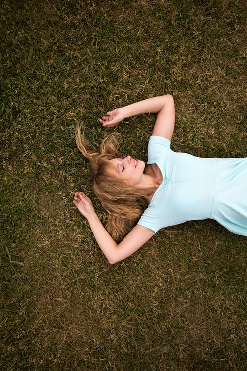 Woman lying on her back on the grass with her eyes closed