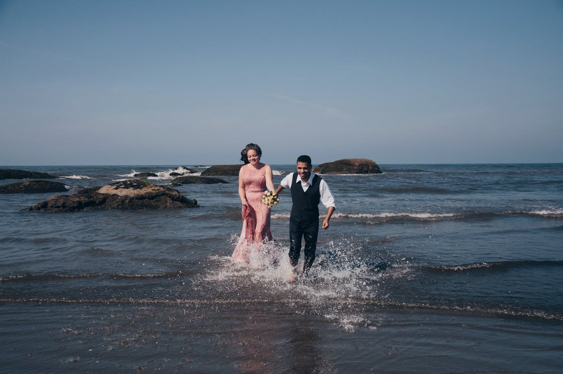 Man and woman running on seashore while holding hands