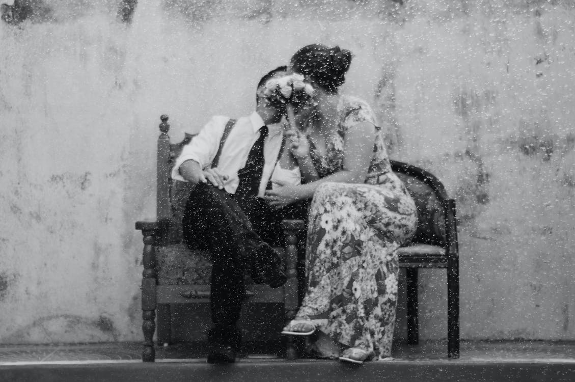 Gray scale photography of a couple kissing covering their faces with Bouquet of Flower