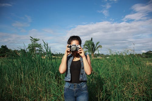Woman Standing on Tall Grasses Taking Photo