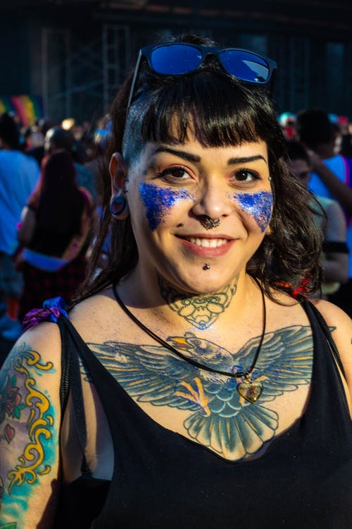 Portrait Photo of Smiling Tattooed Woman in Black Tank Top and Sunglasses with Blue Glitter on Her Cheeks Posing with Crowd of People in the Background