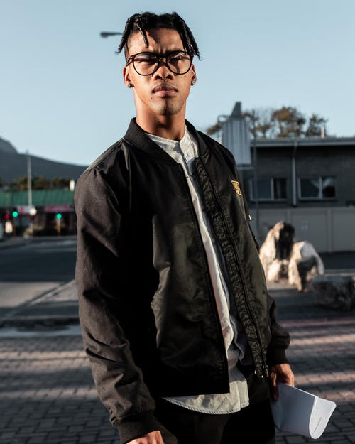 Man wearing black bomber jacket and black framed eyeglasses