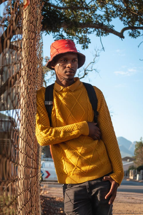 Contemplative black male in yellow knitted sweater and stylish panama hat leaning on grid fence while looking away