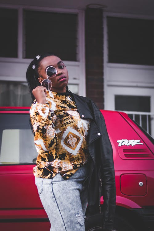 Photo of Woman in Floral Shirt and Blue Jeans Posing With Sunglasses While Standing Beside Red Car